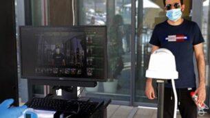 زبون يقف أمام جهاز لفحص درجة حرارة الجسم قبل دخول فرع 'إيكيا' في مدينة نتانيا، 22 أبريل، 2020، بعد أن خففت السلطات من القيود المفروضة خلال أزمة تفشي وباء كورونا.  . (Photo by JACK GUEZ / AFP)