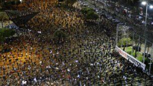 إسرائيليون يرتدون أقنعة واقية وملابس سوداء يشاركون في مظاهرة، في ساحة رابين في تل أبيب، للاحتجاج على ما يعتبرونه تهديدات للديمقراطية الإسرائيلية، على خلفية تحالف وشيك بين رئيس الوزراء بنيامين نتنياهو ومنافسه السابق بيني غانتس، 25 أبريل 2020 (JACK GUEZ / AFP)