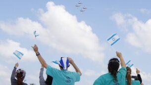 الطاقم الطبي في المركز الطبي شيبا في تل هشومير يلوح بالأعلام الإسرائيلية خلال عرض جوي لطائرات بهلوانية تابعة لسلاح الجو الإسرائيلي فوق المستشفى خلال احتفال إسرائيل بيوم الإستقلال في تحية للطواقم الطبية التي تحارب تفشي جائحة فيروس كورونا، 29 أبريل، 2020.(JACK GUEZ/AFP)