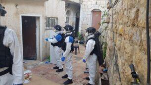 عناصر شرطة إسرائيليون يرتدون ملابس واقية في حي ميا شعاريم بالقدس خلال إلقاء القبض على رجل تم تشخيص اصابته بفيروس كورونا وخالف أوامر الحجر الصحي، 6 أبريل 2020. (Israel Police)