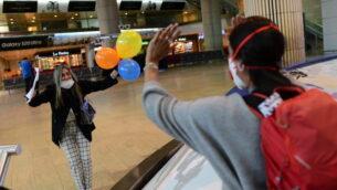 مسافرون إسرائيليون خلال وصول احتفالي إلى مطار بن غوريون، 23 مارس 2020 (Tomer Neuberg / Flash90)