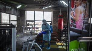 عامل صحة فلسطيني يقوم بإجراء تعقيم وقائي ضد فيروس كورونا في صالة رياضية بمدينة غزة، 15 مارس، 2020.  (Khalil Hamra/AP)