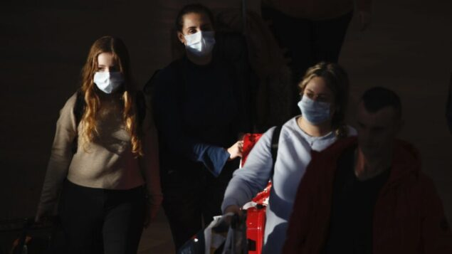 صورة توضيحية: مسافرون يرتدون أقنعة واقية يصلون إلى مطار بن غوريون، 27 فبراير 2020. (AP Photo / Ariel Schalit)