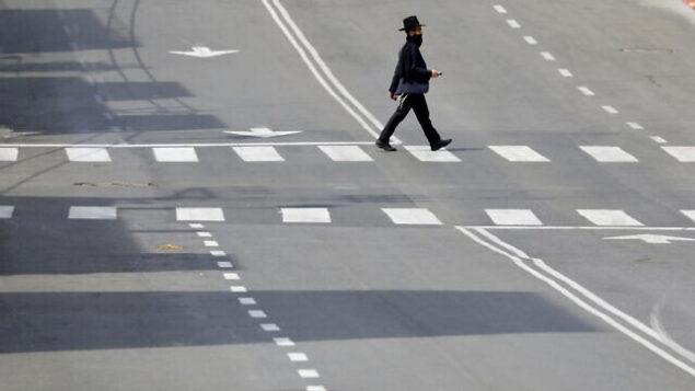 رجل حريدي يعبر شارعا مهجورا في مدينة بني براك، 2 أبريل، 2020.  (AP Photo/Ariel Schalit)