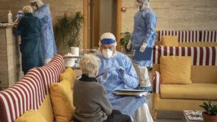 توضيحية: عاملة إغاثة تتحدث مع سيدة مسنة قبل إجراء فحص في بيت مسنين ببرشلونة، إسبانيا، 1 أبريل، 2020.   (AP Photo/Santi Palacios)