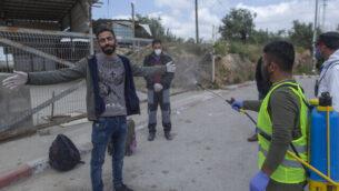 في هذه الصورة التي تم التقاطها في 7 أبريل، 2020 يظهر مسعف من وزارة الصحة الفلسطينية يقوم بإجراءات تعقيم لعمال فلسطينيين للمساعدة في احتواء فيروس كورونا عند دخولهم من حاجز للجيش الإسرائيلي بعد عودتهم من العمل في إسرائيل، بالقريب من قرية نلعين الفلسطينية، غربي رام الله بالضفة الغربية.  (AP Photo/Nasser Nasser)