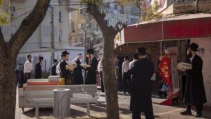يهود متشددون يرتدون أقنعة الوجه يصطفون لشراء البيض في بني براك، 8 أبريل 2020. (AP / Oded Balilty)