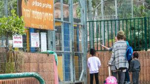طلاب يصلون مدرسة هدار الابتدائية في كفار يونا، 12 مارس 2020 (Chen Leopold / Flash90)