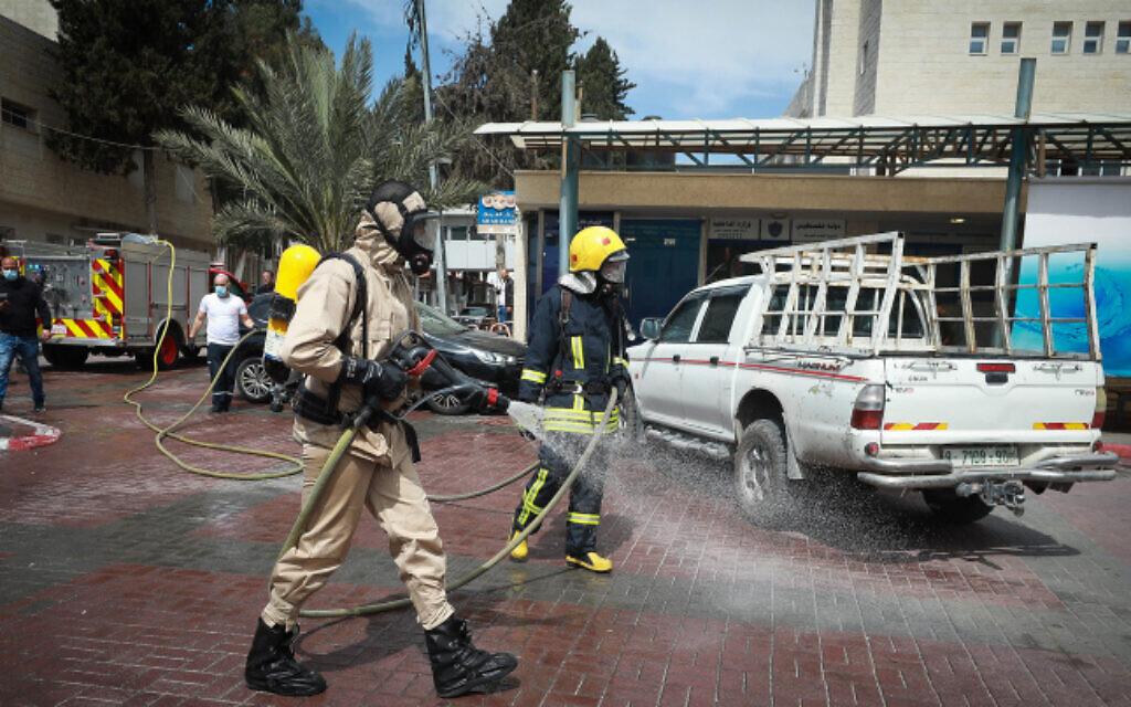 عمال بلدية فلسطينيون يقومون بتعقيم موقف سيارات في أحد مستشفيات مدينة رام الله بالضفة الغربية، 12 مارس، 2020. (Flash90)