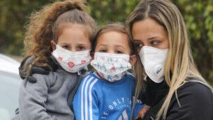 عائلة ترتدي أقنعة الوجه لحماية أنفسهم من فيروس كورونا، 18 مارس 2020. (Yossi Aloni / Flash90)