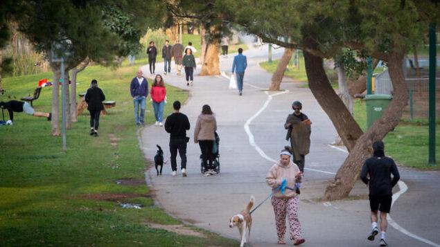 إسرائيليون يقومون بالتنزه مع كلابهم وممارسة الرياضة في حديقة 'هياركون' بتل أبيب، 22 مارس، 2020.   (Miriam Alster/Flash90)