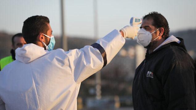 عامل صحة فلسطينية يقوم بإجراءات تعقيم  عند عودتهم من إسرائيل عند مدخل قرية حوسان بالضفة الغربية، 29 مارس، 2020، بهدف منع انتشار فيروس كورونا. (Nati Shohat/Flash90)