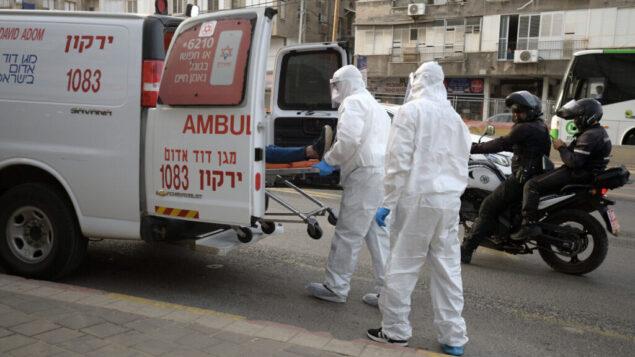 صورة توضيحية: مسعفو نجمة داود الحمراء في ملابس واقية يدخلون رجلًا يشتبه في إصابته بفيروس كورونا الى سيارة إسعاف في بني براك، 31 مارس 2020. (Gili Yaari / Flash90)