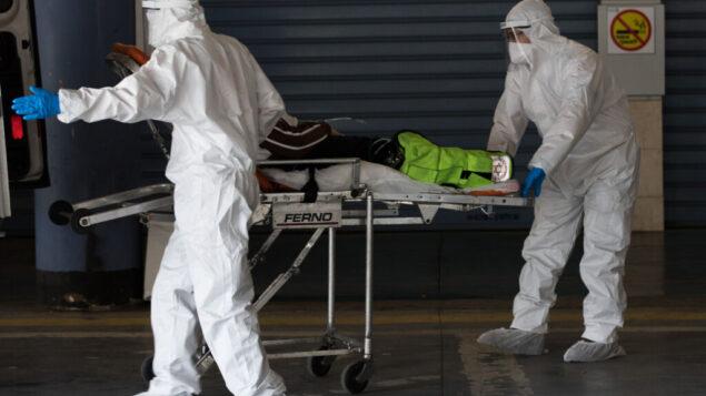 عاملون في نجمة داوود الحمراء يرتدون زيا واقيا خلال نقلهم لمريض يُشتبه بأنه مصاب بفيروس كورونا في مستشفى شعاري تسيدك بالقدس، 3 أبريل، 2020.  (Nati Shohat/Flash90)