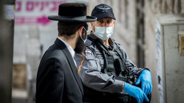 ضباط الشرطة يقومون بإغلاق كنس يهودية وتوزيع غرامات لليهود المتشددين في حي بخاريم في القدس، 6 أبريل 2020. (Yonatan Sindel / Flash90)