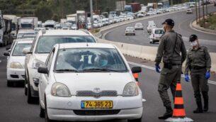 الشرطة تقوم بفحص السائقين عند نقطة تفتيش مؤقتة على الطريق 1 خارج القدس، للتحقق من أن الناس لا يخالفون أوامر الحكومة بإغلاق جزئي لمنع انتشار فيروس كورونا. (Nati Shohat/Flash90)
