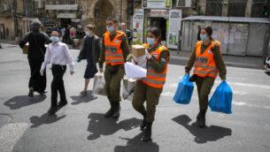 صورة توضيحية: جنود إسرائيليون من قيادة الجبهة الداخلية يوزعون رزم غذائية لكبار السن الذين يضطرون إلى البقاء في المنزل بسبب فيروس كورونا قبل عيد الفصح في القدس، 7 أبريل 2020. (Olivier Fitoussi / Flash90)