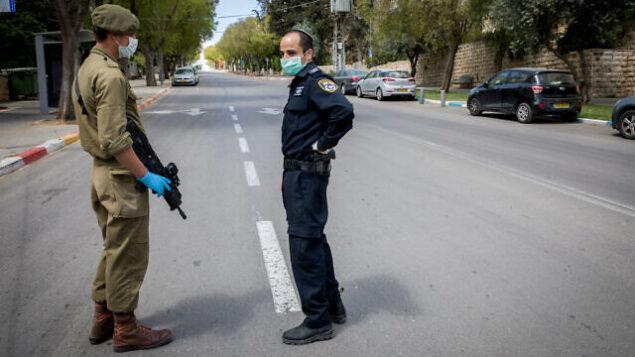 شرطي وجندي إسرائيليان يقفان عند حاجز مؤقت في القدس في 8  أبريل، 2020، قبل بدء حظر تجول كامل في الليلة الأولى من عيد الفصح اليهودي.  (Nati Shohat/Flash90)