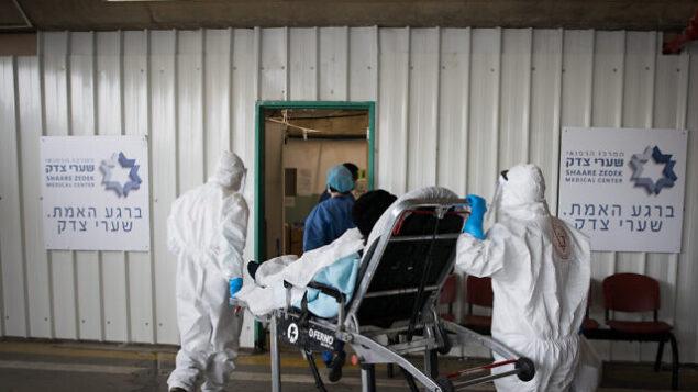 عاملون في نجمة داوود الحمراء يرتدون زيا واقيا خلال نقلهم لمريض يُشتبه بأنه مصاب بفيروس كورونا في مستشفى شعاري تسيدك بالقدس، 10 أبريل، 2020. (Nati Shohat/Flash90)