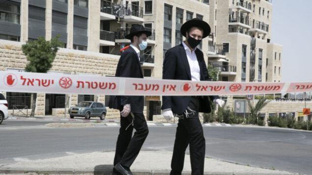 رجال يهود متشددون يعبرون حاجز شرطة في حي يهودي متشدد في القدس، 19 أبريل 2020 (Olivier Fitoussi / Flash90)