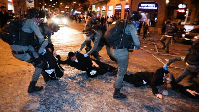 الشرطة تعتقل رجلا يهوديا حريديا في حي مئة شعاريم، في أعقاب احتجاجات ضد القيود المفروضة بسبب فيروس كورونا، 19 أبريل، 2020. ( Olivier Fitoussi/Flash90)