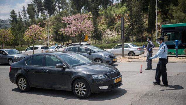 عناصر الشرطة في حاجز مؤقت عند مدخل حي راموت في القدس، 12 أبريل 2020 (Yonatan Sindel/Flash90)