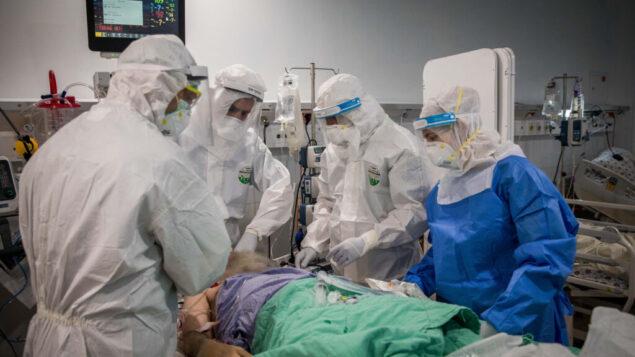"""صورة توضيحية: طاقم طبي يقدم العلاج لمريض مصاب بفيروس كورونا (COVID-19) في وحدة فيروس كورونا في المركز الطبي """"معياني هيوشاعا""""، بني براك، 13 أبريل، 2020.  (Nati Shohat/Flash90)"""