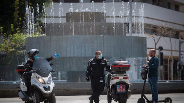 الشرطة الإسرائيلية تقوم بدورية في ميدان ديزنغوف بتل أبيب للتأكد من التزام المواطنين بأوامر الحكومة بشأن الإغلاق الجزئي الذي يهدف إلى منع انتشار فيروس كورونا، 14 أبريل، 2020.  (Miriam Alster/Flash90)