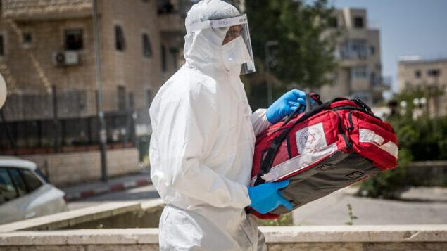 عامل في نجمة داوود الحمراء يرتدي زيا واقيا كإجراء وقائي ضد فيروس كورونا يصل لفحص مريض يُشتبه بإصابته بفيروس كورونا، في القدس، 14 أبريل، 2020. (Yonatan Sindel/Flash90)
