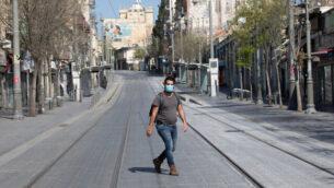 رجل يرتدي قناعا واقيا يسير في أحد شوارع القدس الخالية، 14 أبريل، 2020. (Olivier Fitoussi/Flash90)