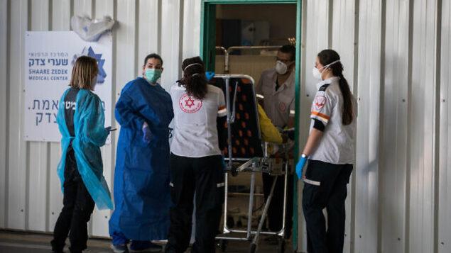 الفريق الطبي في مستشفى شعاري تسيدك بالقدس يستقبل مريضا يُشتبه بإصابته بفيروس، 16 أبريل، 2020.  (Nati Shohat/Flash90)