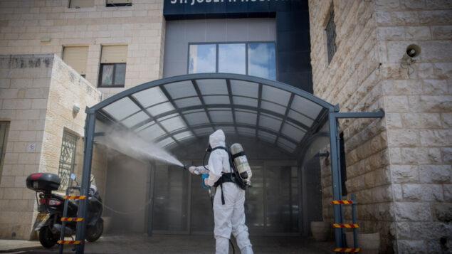رجل إطفاء إسرائيلي يقوم بتطهير مدخل مستشفى سانت جوزيف في القدس الشرقية، 16 أبريل 2020 (Yonatan Sindel/Flash90)