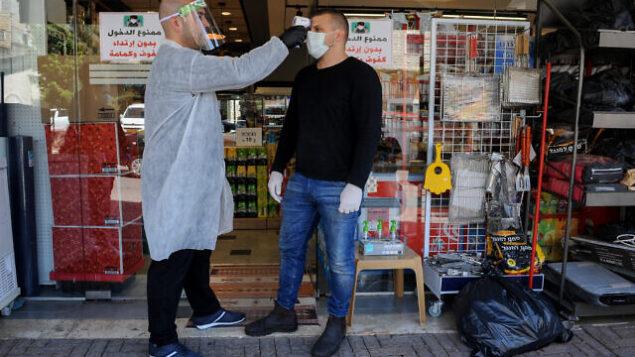 عامل يقوم بفحص درجة حرارة أحد الزبائن في أحد المحلات التجارية في قرية دير الأسد شمالي إسرائيل، 18 أبريل، 2020. (Basel Awidat/Flash90)