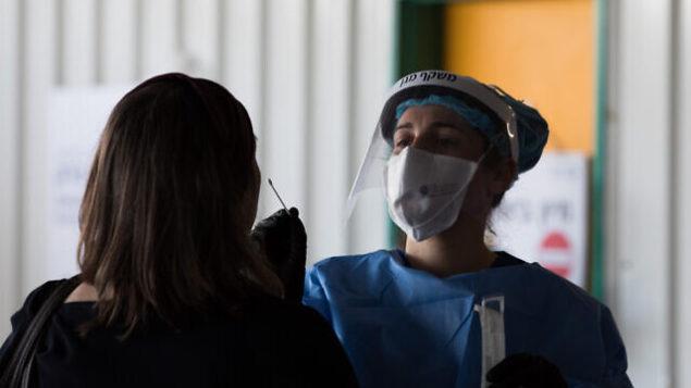 عضو فريق طبي من مستشفى شعاري تسيدك في زي واق تجري فحص للكشف عن فيروس كورونا (كوفيد 19)، خارج وحدة فيروس كورونا في المستشفى بالقدس، 20 أبريل، 2020.  (Nati Shohat/Flash90)