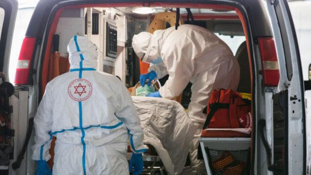 مسعفو نجمة داود الحمراء في ملابس واقية يقومون بإجلاء مريض مشتبه في إصابته بفيروس كورونا إلى وحدة فيروسات كورونا في مستشفى شعاريه تسيديك في القدس، 20 أبريل 2020. (Nati Shohat / Flash90)