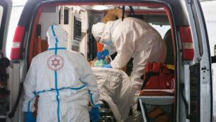 مسعفان من نجمة داوود الحمراء بزي واق يقومان بنقل مريض يُشتبه بإصابته بفيروس كورونا إلى وحدة فيروس كورونا في مستشفى شعاري تسيدك بالقدس، 20 أبريل، 2020. (Nati Shohat/Flash90)