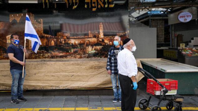 اشخاص يقفون في سوق محانيه يهودا في القدس، اثناء انطلاق صفارات الإنذار لمدة دقيقتين في جميع أنحاء إسرائيل بمناسبة يوم ذكرى المحرقة، 21 أبريل 2020 (Olivier Fitoussi / Flash90)