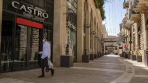 رجل يسير من أمام المحلات التجارية المغلقة في 'ماميلا مول' بالبلدة القديمة في القدس، 22 أبريل، 2020. (Olivier Fitoussi/Flash90)
