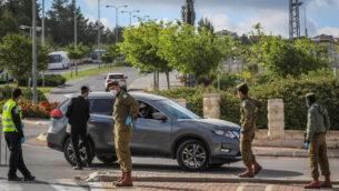 شرطيون وجنود إسرائيليون يقفون عند حاجز في مدخل مدينة بيت شيمش، 4 أبريل، 2020. (Yaakov Lederman/Flash90)