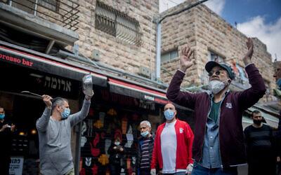 أصحاب أكشاك في سوق محانيه يهودا يحتجون على الإغلاق المستمر لمحلاتهم في خضم أزمة جائحة فيروس كورونا، 26 أبريل، 2020. (Yonatan Sindel/Flash90)