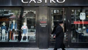 صورة توضيحية: رجل يمشي أمام فرع مغلق لشبكة الأزياء 'كاسترو' في وسط مدينة القدس في 26 أبريل 2020 (Yonatan Sindel/Flash90)