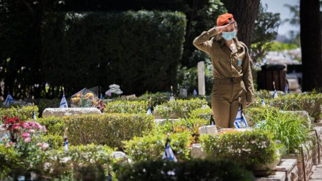 جندية إسرائيلية تضع الزهور عند قبور الجنود الإسرائيليين القتلى في مقبرة جبل هرتسل العسكرية، 27 أبريل 2020. (Yonatan Sindel / Flash90)