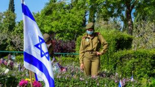 جنود إسرائيليون بالقرب من قبور الجنود الذين سقطوا في مقبرة كريات شاؤول العسكرية بينما تحيي إسرائيل يوم الذكرى للجنود الذين سقطوا وضحايا الهجمات، 28 أبريل 2020. (Avshalom Sassoni / Flash90)