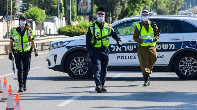 شرطيون وجنود إسرائيليون يقفون عند حاجز على الطريق المؤدي إلى المقبرة العسكرية 'كريات شاؤول' مع إحياء إسرائيل ليوم الذكرى، 28 أبريل، 2020. (Avshalom Sassoni/Flash90)