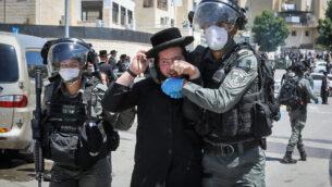 مواجهة بين عناصر الشرطة ورجل حريدي خلال مداهمة في أحد أحياء مدينة بيت شيمش في 28 أبريل، 2020.(Yaakov Lederman/Flash90)