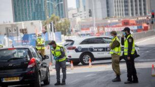 الشرطة تقوم بتطبيق الإغلاق بسبب تفشي جائحة فيروس كورونا عند حاجز على طريق 'بيغن' في تل أبيب، 29 أبريل، 2020.  (Miriam Alster/Flash90)