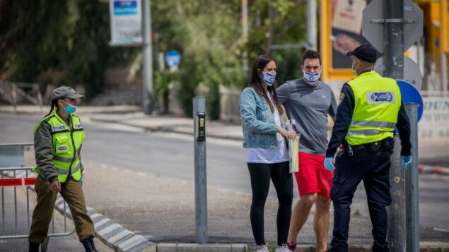 الشرطة عند أحد الحواجز لتطبيق الإغلاق بسبب تفشي فيروس كورونا، القدس، 29 أبريل، 2020.  (Yonatan Sindel/Flash90)