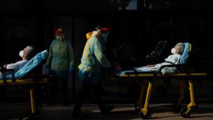 عمال صحيون يدفعون نقالات مع اثنين من سكان دار مسنين ثبتت إصابتهما بفيروس كورونا الجديد في برشلونة، إسبانيا، 11 أبريل 2020. (AP / Felipe Dana)
