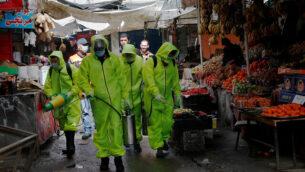 عمال يرتدون زيا واقيا يقومون برش مطهرات كإجراء وقائي ضد فيروس كورونا في السوق الرئيسية بمدينة غزة، 27 مارس، 2020. (AP/Adel Hana)