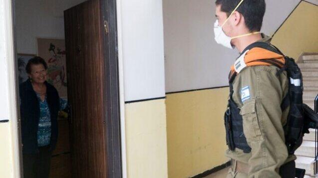 جندي إسرائيلي يقوم بزيارة سيدة إسرائيلية مسنة في إطار الجهود التي يبذلها الجيش لمساعدة السكان الأكثر عرضة للخطر في خضم تفشي فيروس كورونا، 2 أبريل، 2020. (Israel Defense Forces)